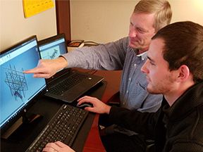 Owner and worker looking at CAD mechanical drawing on computer