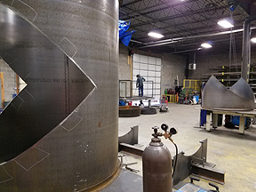 Metal fabrication - assorted tanks, fixture, etc. with worker in background